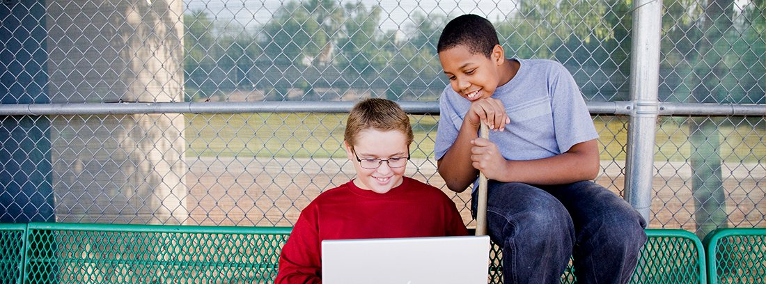 two students at the park with a laptop