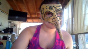Girl wearing golden mask with pointed nose