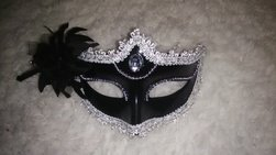 Black mask with silver glitter lining and a black feather on the left side.